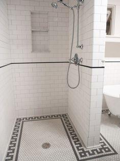 I like the hand shower on slider bar, subway tile and tiled niche. Greek key floor tile border