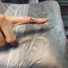 Tiny camera finger tattoo done by Cam Whaley at Walls of Wonder Tattoo in Dover, DE.