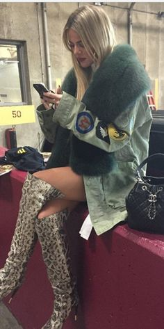 Who made  Khloe Kardashian's green coat, snake boots, and black quilted backpack?