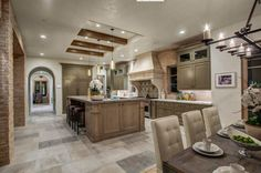 The rich variety of materials in this kitchen are all pitched toward soft, neutral hues, with rich natural wood cabinetry, marble countertops, and a large format tile flooring spanning the spectrum between light brown and light grey. The massive island at center features in-kitchen dining space, standing directly below a ceiling cut-out with exposed wood beams.