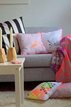 grey sofa with pillows and throw blanket with neons