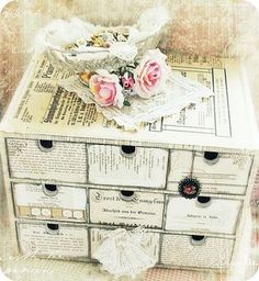 Box from Ikea, covered painted white, decopodged with book pages & print, destressed, and it looks authenticl & old!