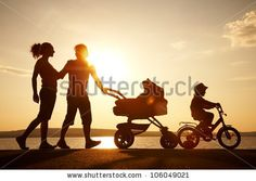 Silhouettes of happy parents having good time with their little children on the seacoast - stock photo