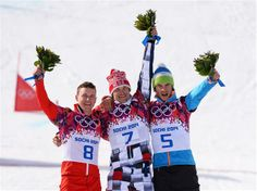 (L-R) Silver medalist Nevin Galmarini of Switzerland, gold medalist Vic Wild of Russia and bronze medalist Zan Kosir of Slovenia celebrate on the podium, during the flower ceremony for the Snowboard Men's Parallel Giant Slalom Finals. Sochi 2014 Day 13 - Snowboard Men's Parallel Giant Slalom.