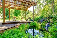 Picturesque backyard farm garden with small pond and patio area. Reasons you should have a pergola in your yard. #pergola #landscape #dan330 http://livedan330.com/2015/03/26/include-outdoor-pergola-garden/