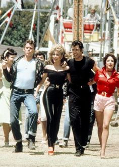 "From left, actors Jeff Conaway, Olivia Newton-John, John Travolta and Stockard Channing walk arm in arm at a carnival in a still from the 1978 movie musical ""Grease. Olivia Newton John, John Travolta, Movies Showing, Movies And Tv Shows, Film Scene, Movie Stars, Movie Tv, Movie Theater, Theatre"
