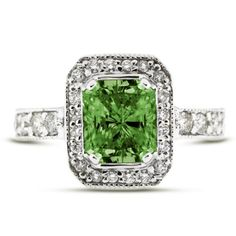 Vintage Radiant Green Diamond Engagement Ring - A classy 14k Gold Halo Style Vintage Radiant Green Diamond Engagement Ring that features a 2.11 Carat Rectangular Shaped Radiant Cut Diamond set within the center along with an additional 28 small white diamonds on it's side. The center gemstone is set in a 4-Prong setting & the accent diamonds are in a Pave settings. The total gem weight for the ring is 2.74 carats & is set in 14k White Gold. The diamonds are 100% natural…