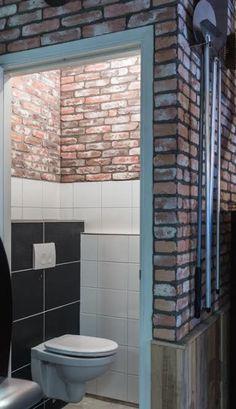 Een zwart witte wc krijgt sfeer door een bontgekleurde robuuste muur