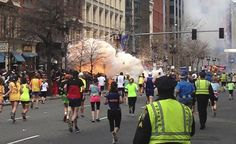 Runners continue to run towards the finish line as an explosion erupts at the finish line of the Boston Marathon