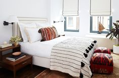 Textiles carry the eye in the white-walled master bedroom. On the windows, Roman shades from the Shade Store continue a theme of black details with stitched borders, tying into the tasseled quilt and bronze accents. By the bed, shaded sconces contribute a contemporary touch above yesteryear's tiered nightstands.