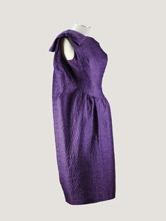 Balenciaga Haute Couture,   A purple cloqué silk cocktail dress with  aysmmetric draped 'sack' back, 1962.