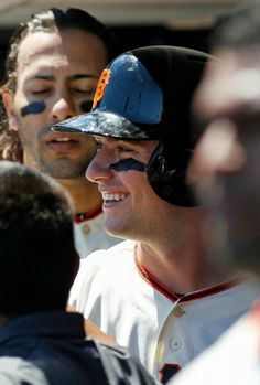 San Francisco Giants' Andrew Susac smiles in the dugout after scoring against the Philadelphia Phillies during the second inning of a baseball game, Sunday, Aug. 17, 2014 in San Francisco. Giants Michael Morse, who scored on the same hit stands in the background. (AP Photo/George Nikitin)