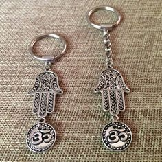 Silver Hamsa and Ohm Keychain. Silver Hamsa Keychain / Hamsa Key Chain / Ohm Keychain / Ohm Key Ring / Ohm Key Chain/ Yoga Keychain /Yoga Key Chain You have your choice of key chain and charm only: 4 1/4 inches long key chain with charm and rolo chain: 3 1/4 inches long. • Hangs from silver plated brass chunky rolo chain that has been soldered for strength and lengthy ownership. • Rolo chain is wide enough to add more keyrings to fit your specific needs. • Silver plated steel key chain is…