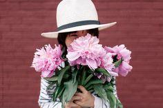 Cute mixed race boy holds pink flowers in front of brick wall by KelliSeegerKim   Stocksy United