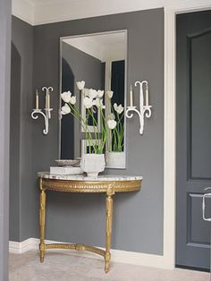 small entry gray wall with gold and marble console, candle sconces