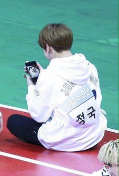 Jungkook might be looking at a funny photo of Jin, it looks like it made his day. :)
