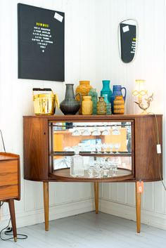 Mid Century Modern bar is a corner liquor cabinet that resembles some of these vintage TV console conversions at: http://homebars.barinacraft.com/post/32666606235/old-tv-conversions-to-home-bars  .. Stock in this unit spins on a lazy susan for easy access and has curved sliding doors which can be closed when not in use.