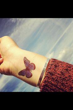Purple butterfly wrist tattoo