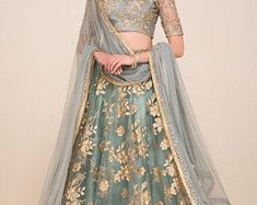 The bardot neckline blouse is adorned with floral sequin embroidery. It is paired with a net flared embroidered lehenga and net dupatta. gold grey blue silver by collective lengha Indian Bridal Lehenga, Indian Bridal Outfits, Indian Fashion Dresses, Indian Gowns, Indian Designer Outfits, Indian Attire, Indian Wear, Pakistani Bridal, Pakistani Dresses