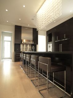 Super contemporary kitchen with glass lighting over island, sleek stainless range hood, hardwood floors #home #remodel #kitchen #bathroom #interiors www.jimhicks.com