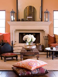 Peach walls and terra-cotta hued cushions infuse warmth into this living room. - Traditional Home ®/ Photo: Michael Garland / Design: Jayne and Joan Michaels