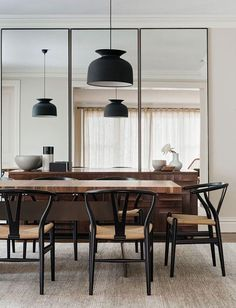 Modern dining space with black pendant lights, black midcentury dining chairs and floor to ceiling oversized mirrors.:
