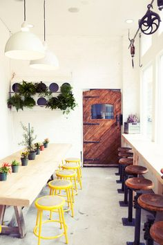 Vogue Daily — cafe in NYC but i like the mix of white, dark stained wood and yellow