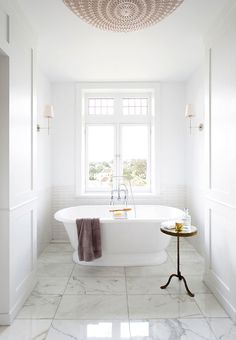 Cool whites … beautiful large marble floor tiles and marble vanity counters in this simply styled, light-filled bathroom. Elegant tall windows and white subway tiles, lining the shower and surrounding