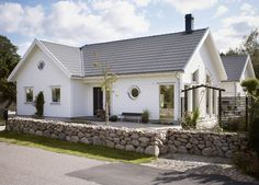 Denna 1-plansvilla, med krispigt vit liggande träpanel, ljusgrå takpannor och stora ljusinsläpp, för tankarna till klassisk och tidlös skandinavisk design.