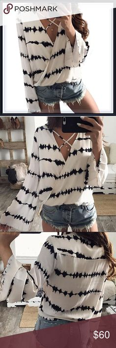 White & Black Bell Sleeve Criss Cross Top ➖SIZE: Small, Medium, Large, XL/1X  ➖STYLE: A white Blouse with a criss cross at the neckline along with black stripes that have an artistic splattered look to them as well as bell sleeves  ❌NO TRADE  135409 Tops Blouses