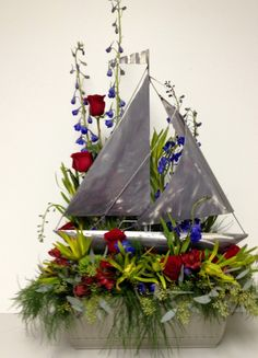"This piece was for behind a cremation urn. The sail boat is metal and the over all arrangement was about 36"" tall and 18"" across. The flowers were; red roses, blue delphinium, red, alstromeria, safari sunset, tree fern and green ball dianthus."