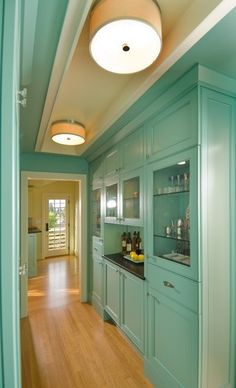 This classic butler's pantry shares its cabinetry finish-dont like this- with the adjacent kitchen, creating a desirable visual flow between the two rooms. This is a traditional location and design plan for a butler's pantry. - Maybe make opposite wall (hidden here) entry storage because we would loose it otherwise.