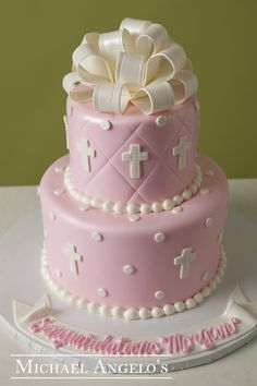 Polka Dots & Cross Cut-Outs #17Religious This cake creation is made up of two layers iced in pink fondant. The stitching is a creative way to add some texture to a layer. The cross and polka dot cut outs also add some depth and the fondant bow is a great way to top off the cake. Perfect for any religious occasion and comes in any color of choice.