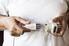The hands of an old woman are connecting two electrical plugs one to the other — Stock Photo © carlotoffolo #148618019
