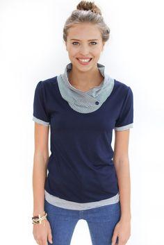 Süßes Shirt aus dunkelblauem Viskosejersey. Der locker fallende Kragen ist aus dunkelblau-weiß gestreiftem Viskosejersey. Die kurzen Puffärmelchen und der Knopf am Ausschnitt sind weitere...