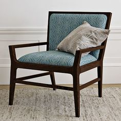 I like the combo of low angles on the chair, dark wood, teal fabric.... silvery pillow....