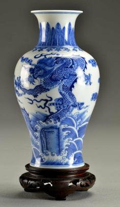 "Chinese Blue & White Porcelain Vase Finely painted to depict five-clawed dragons contesting a flaming pearl above crashing waves, raised on short foot ring, base six-character marked, now on a hardwood stand, 7.75""H including stand."