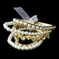 """This vintage style bracelet set consists of five separate strands tied together with a charming white bow. Two ivory faux pearl strands, two ivory faux pearl strands with gold plating and a single strand of glistening rhinestones set in a gold antique style design. This beautiful set is a perfect choice for your prom, wedding or any special event. Makes a great bridesmaid gift too!  Size: All 5 bracelets together measure 1.25"""" wide and will stretch to fit most wrists"""