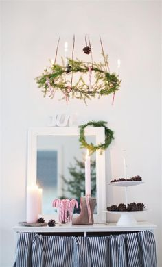 Simple and festive decorating ideas from a Scandinavian home: evergreen sprigs, pine cones and candy canes.