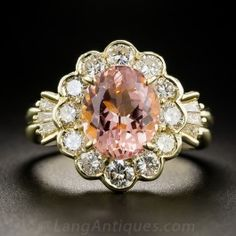 A bright and lively, peachy pink, faceted oval topaz, weighing 3.43 carats, glistens from within a sparkling white diamond halo supported on each side by fans of baguette diamonds, in this cheerful, charming, and exceedingly well-priced estate jewel crafted in gleaming 18K yellow gold. 1.44 carats total diamond weight. Currently ring size 6.