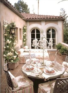 dreamy outdoor dining, with climbing roses, daybeds and lovely windows