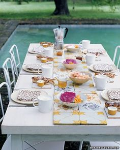 What could be easier than floating a few fresh garden roses, nasturtiums, and phlox in small bowls of water? But that's more than enough when they're placed upon a platform of pretty vintage tiles that serves as both a table runner and a trivet.