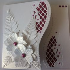 used marianne creatables anja edger. flowers and a memory box leaf die, plus brads,gems and brads. Die cut an edge on a blank card and a separate border. put coloured paper underneath both. Stuck one edge to back inside edge and then another one for the inside edge. Added the flowers and leaves to finish