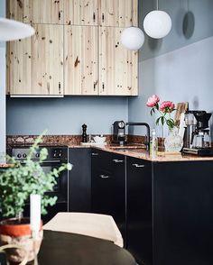 Det er nok de færreste som ville turde at kombinere de lyse overskabe, med de sorte køkkenlåger og den brune bordplade i marmor. Men smukt er det! Foto: Entrance Fastighetsmäkleri #køkken #pendel #boligmagasinet