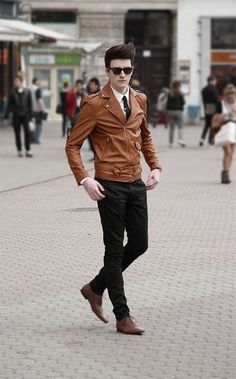 Try pairing a tobacco leather jacket with black chinos to get a laid-back yet stylish look. Throw in a pair of brown leather oxford shoes for a masculine aesthetic.   Shop this look on Lookastic: https://lookastic.com/men/looks/biker-jacket-dress-shirt-chinos-oxford-shoes-tie-sunglasses/13334   — Black Sunglasses  — White Dress Shirt  — Black Tie  — Tobacco Leather Biker Jacket  — Black Chinos  — Brown Leather Oxford Shoes