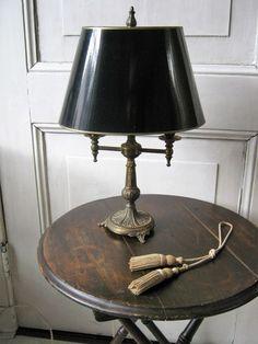 messing bouillottelamp 2-lichts - ovaal Frankrijk 2e helft 20e eeuw Vintage bouillottelamp/bureaulamp typisch Franse tafellamp sfeermaker in elk type interieur. Het ovale kapje van zwarte lak is destijds op maat gemaakt in een kappenatelier vanwege de aansluiting aan de bovenkant (knop support) ; wel gebruikt maar in een goede staat. De kap heeft een binnenkant van goudfolie voor optimale zachte verlichting.. De lampenvoet is van koper met een enigszins doorleefd patina. De totale hoogte is…