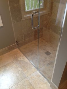 Large stone tiled shower with a semi-frameless door and silver c-style handle | Plymouth Project | Spring/Summer