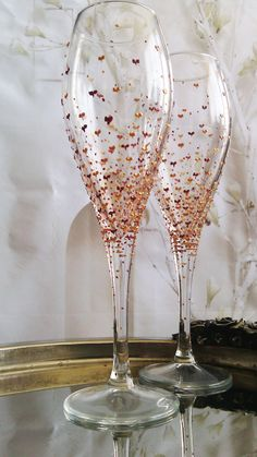 Beautiful set of 2 wine glasses with delicate hand painted hearts and dots in copper and gold.    Hand wash only.