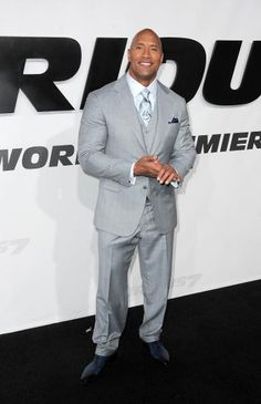 This very large man must have every one of his suits custom made for him because Big & Tall stores don't carry exquisitely tailored three-piece ensembles such as this one. Though he's a enforcer in the movie, his floral light blue patterned tie and navy pocket square offer a lighthearted touch.