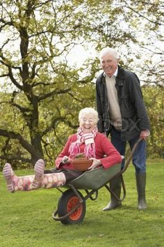 'Senior Couple Man Giving Woman Ride In Wheelbarrow' - Rockin' Years!